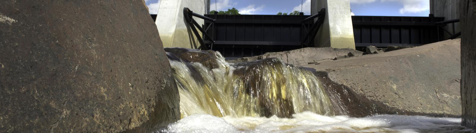 photo water flowing through a gate of the dam